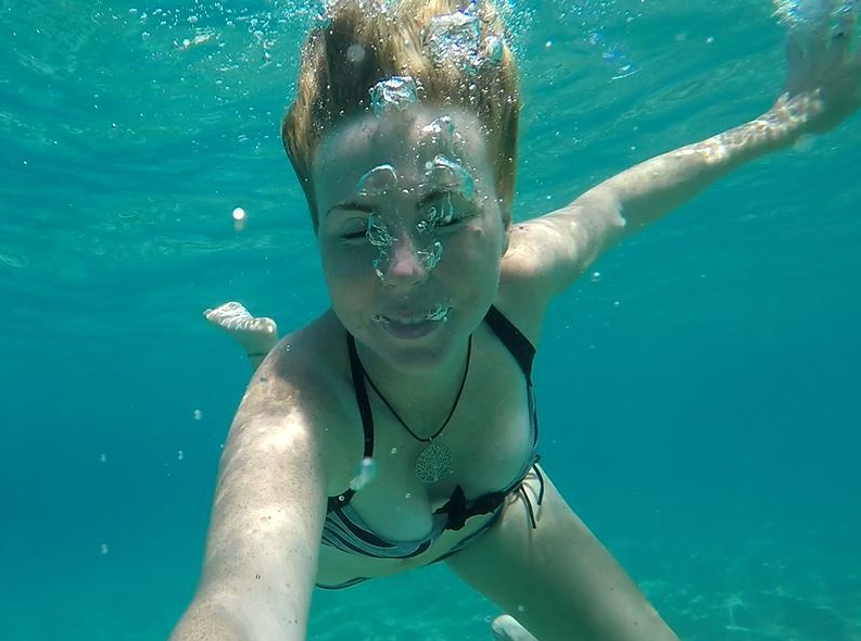Girl blowing bubbles under water in Hawaii