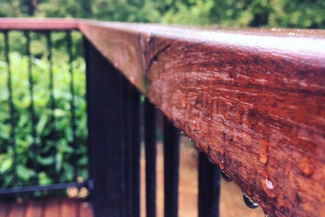 Rain drops clinging to the banister of a deck above a yard of scorched grass